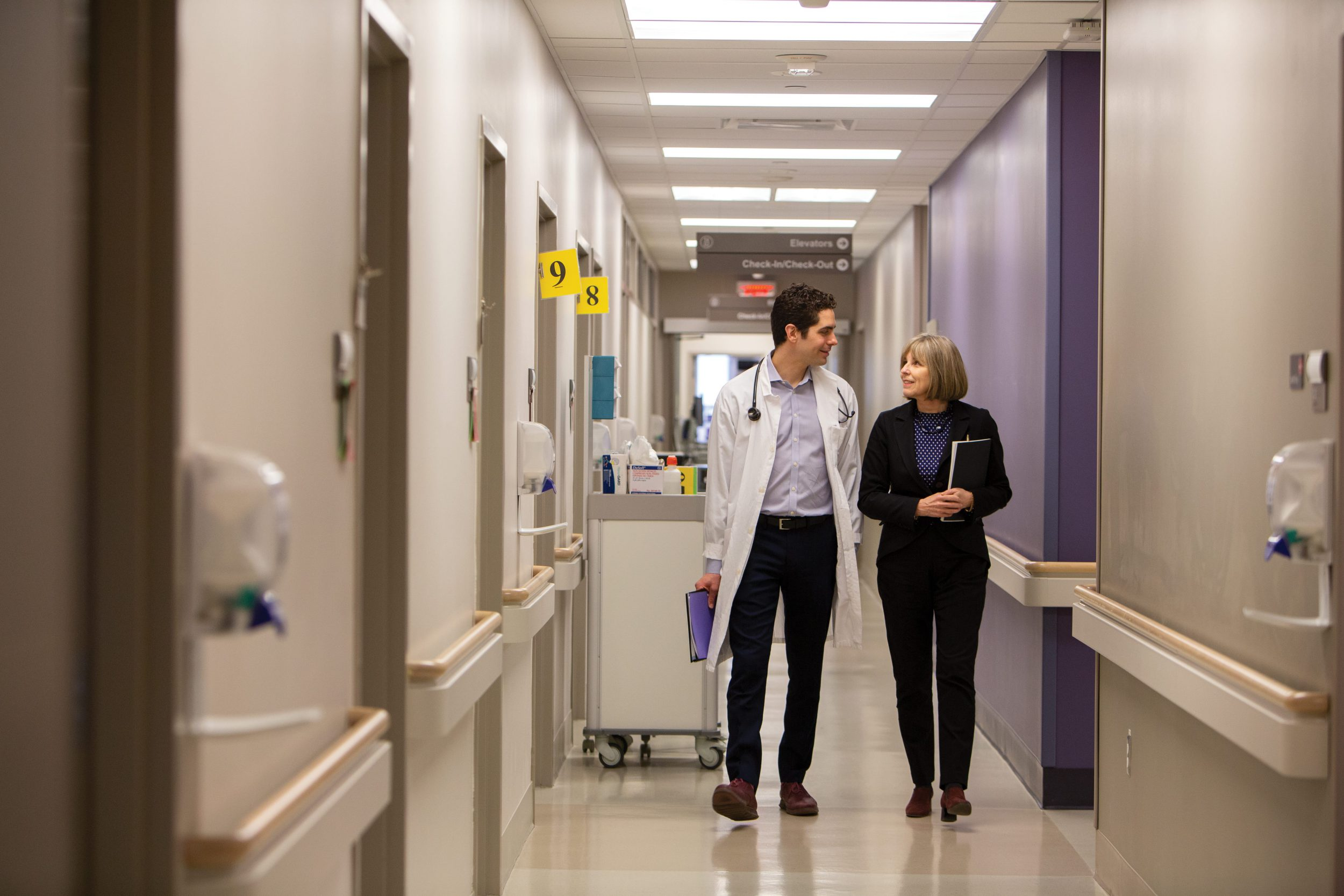 Dr. Stall and Dr. Rochon walk down a hallway