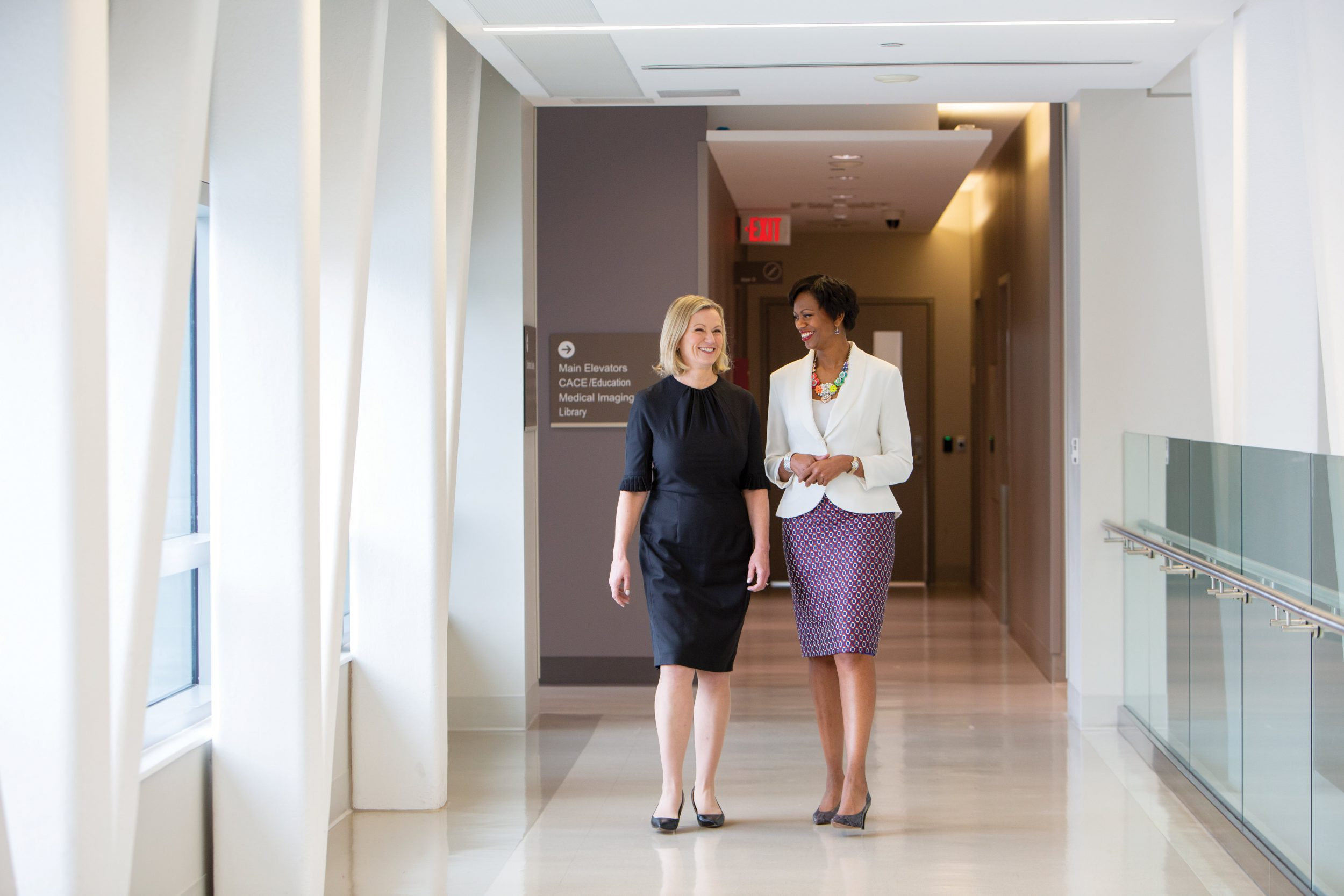 Heather McPherson, CEO and President, Women's College Hospital and Jennifer Bernard, CEO & President of Women's College Hospital Foundation walk down a brightly lit hospital hallway