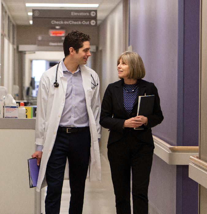 Dr. Nathan Stall and Dr. Paula Rochon walking down a hallway